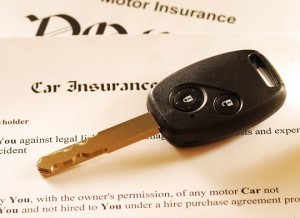 Car key on an insurance policy. Toned warm.